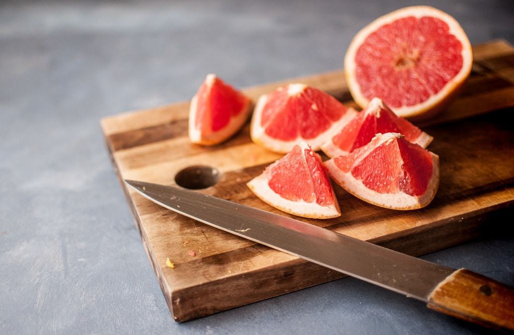 Chopped grapefruit on wooden chopping board
