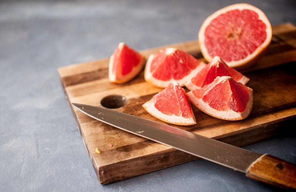 Chopped grapefruit on wooden chopping board