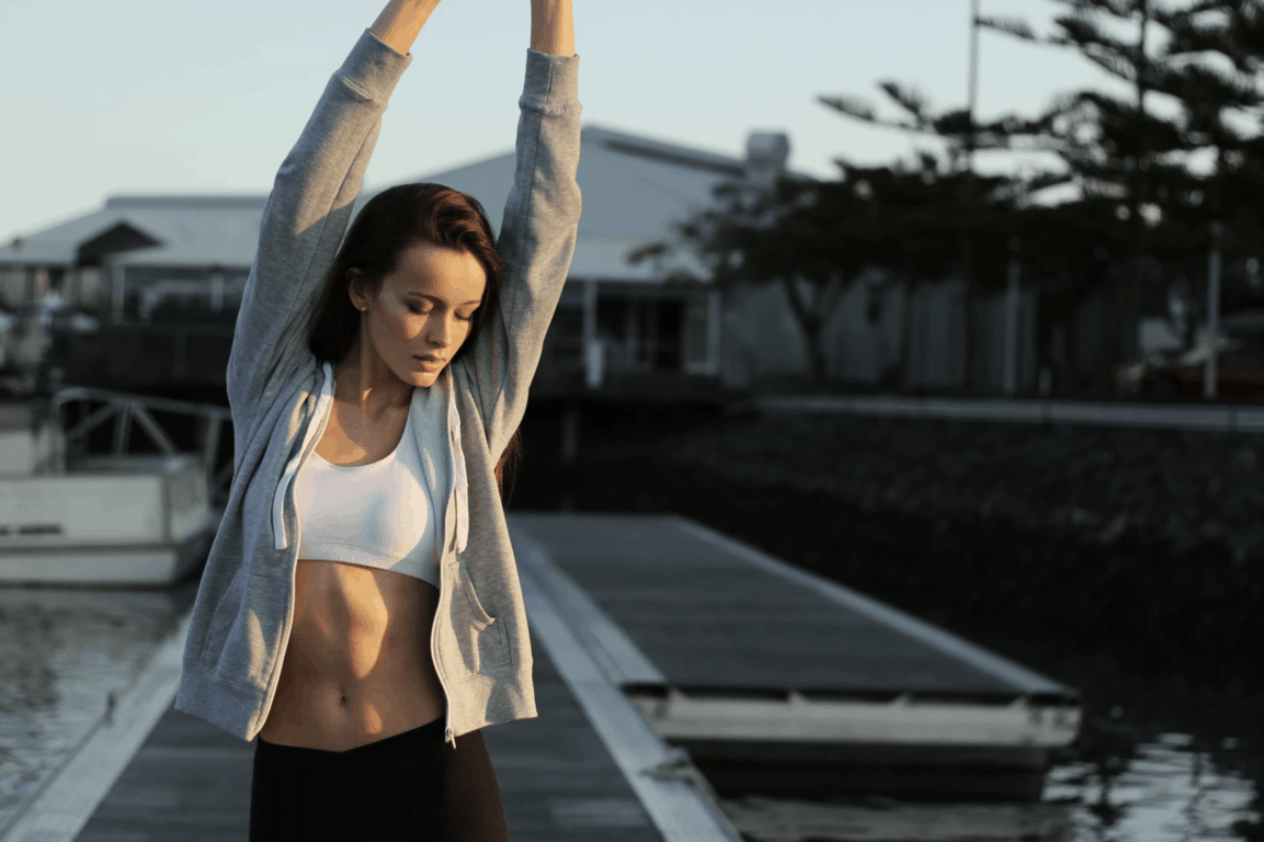 coolsculpting - women stretching showing her fit belly.