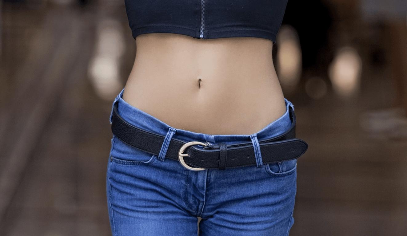 flat tummy tea - women in jeans showing her belly