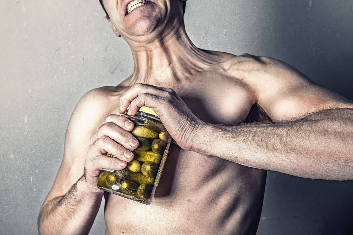 man opening a bottle of pickles