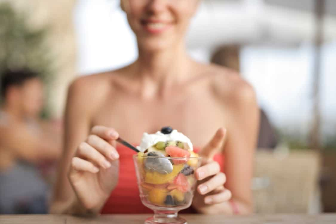 woman eating ice cream and fruits. Fruit is an important part of 21 Day Fix recipes