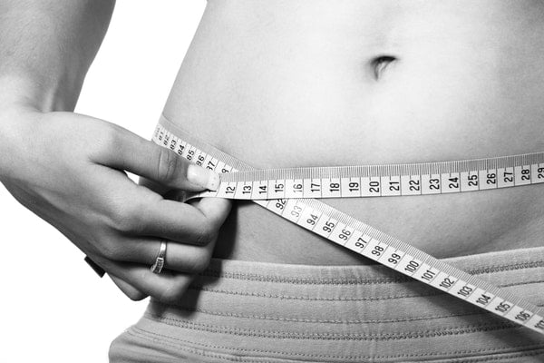 Lady measuring belly with tape